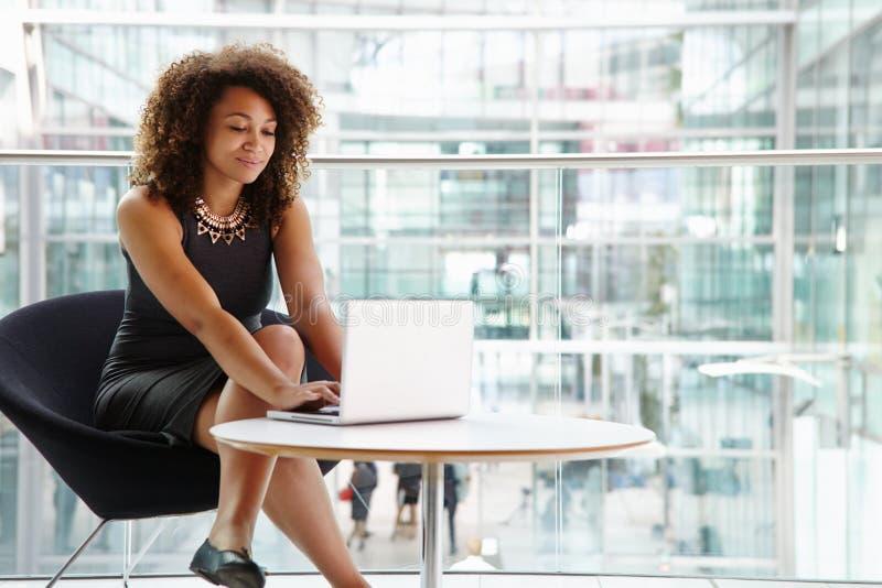 Mulher de negócios nova que usa o laptop no interior moderno imagem de stock royalty free