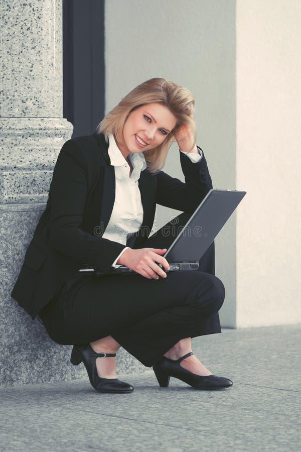 Mulher de negócios nova que usa o portátil no prédio de escritórios fotografia de stock