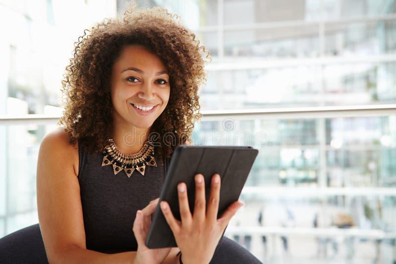 Mulher de negócios nova que usa o tablet pc no interior moderno foto de stock royalty free