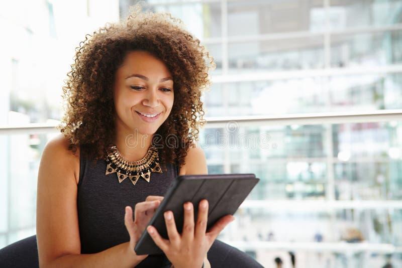 Mulher de negócios nova que usa o tablet pc no interior moderno fotografia de stock