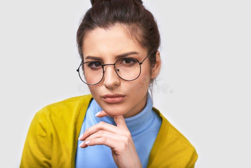 Mulher de negócios nova séria que veste a blusa azul e monóculos transparentes redondos, com espaço vazio branco da cópia para se fotos de stock
