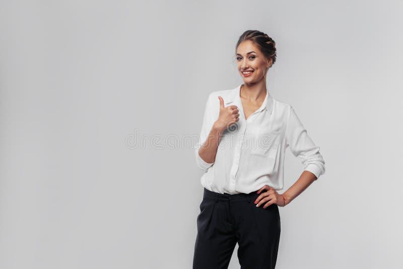 Mulher de negócios nova segura que dá os polegares acima contra um gra foto de stock royalty free