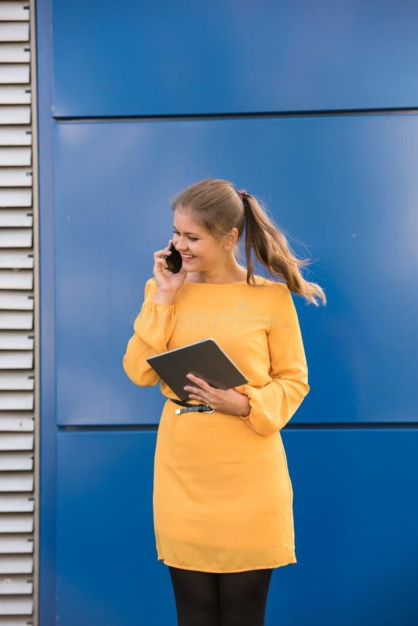 Mulher de negócios nova de sorriso no telefone que guarda a tabuleta imagens de stock royalty free