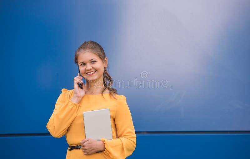 Mulher de negócios nova de sorriso no telefone que guarda a tabuleta imagem de stock royalty free