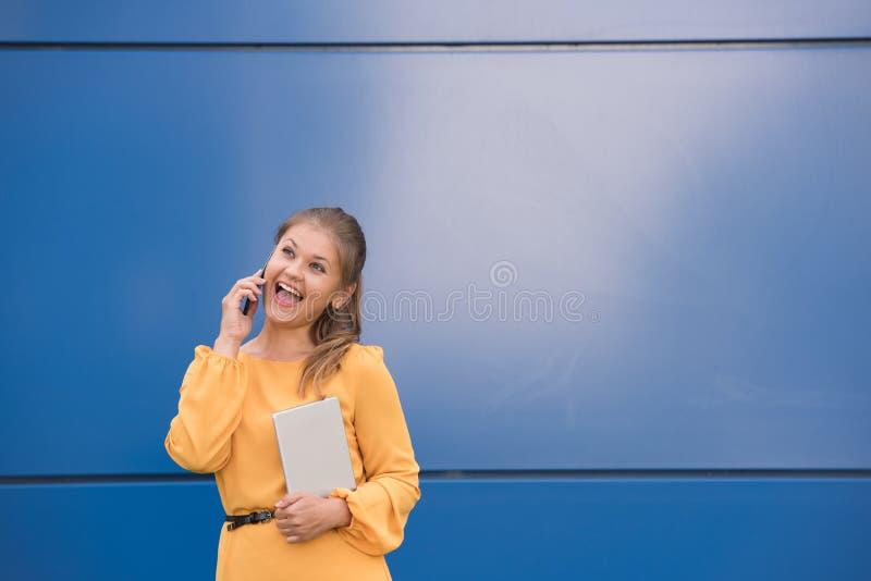 Mulher de negócios nova de sorriso no telefone que guarda a tabuleta fotos de stock royalty free