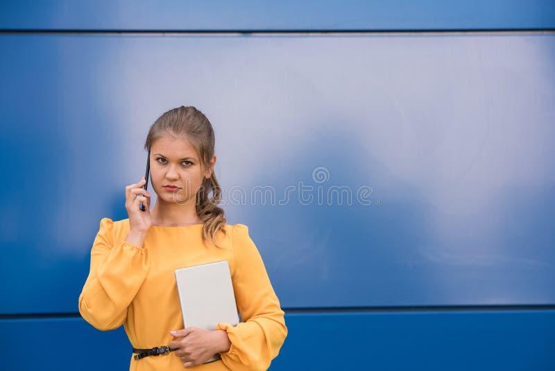 Mulher de negócios nova de sorriso no telefone que guarda a tabuleta imagens de stock