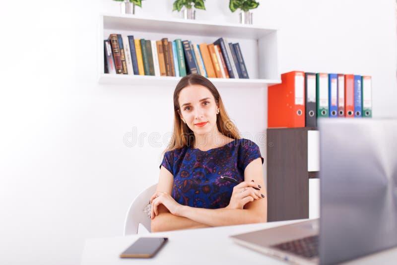 Mulher de negócios nova de sorriso que senta-se na mesa de escritório que trabalha em um portátil, olhando a câmera foto de stock