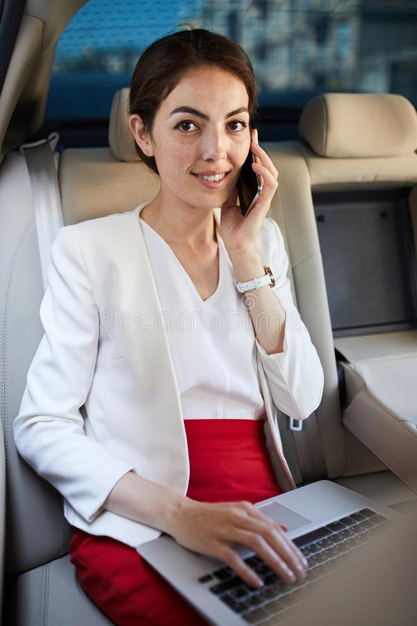 Mulher de negócios nova Speaking pelo telefone no táxi imagem de stock