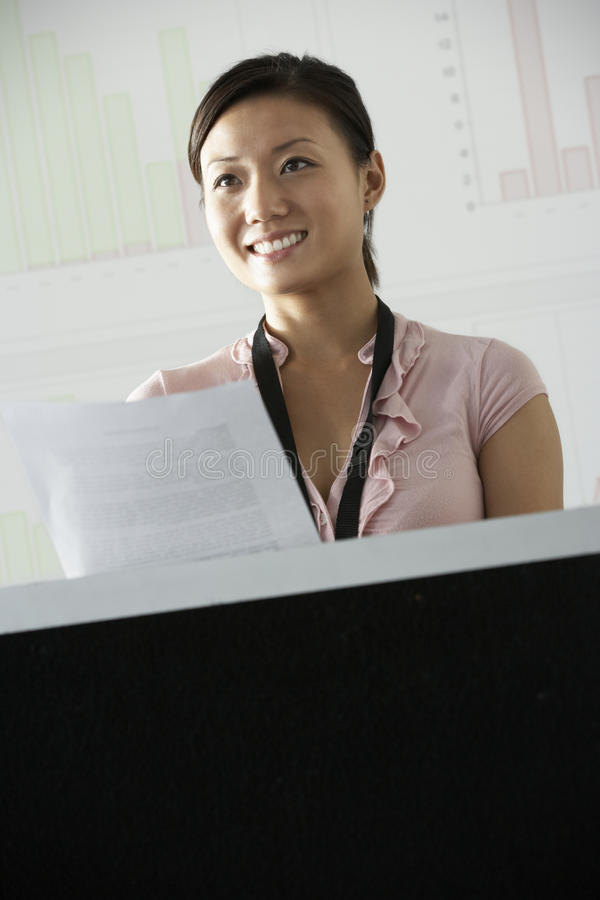 Mulher de negócios nova Standing At Podium que entrega a apresentação na conferência fotografia de stock