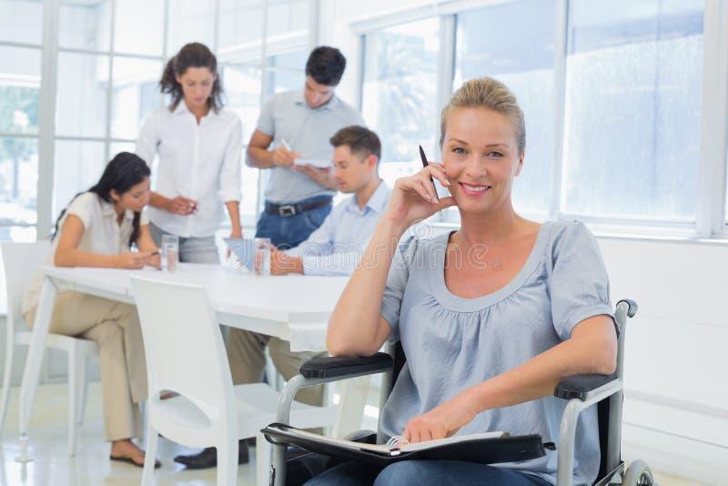 Mulher de negócios ocasional na cadeira de rodas que sorri na câmera com a equipe atrás dela foto de stock royalty free