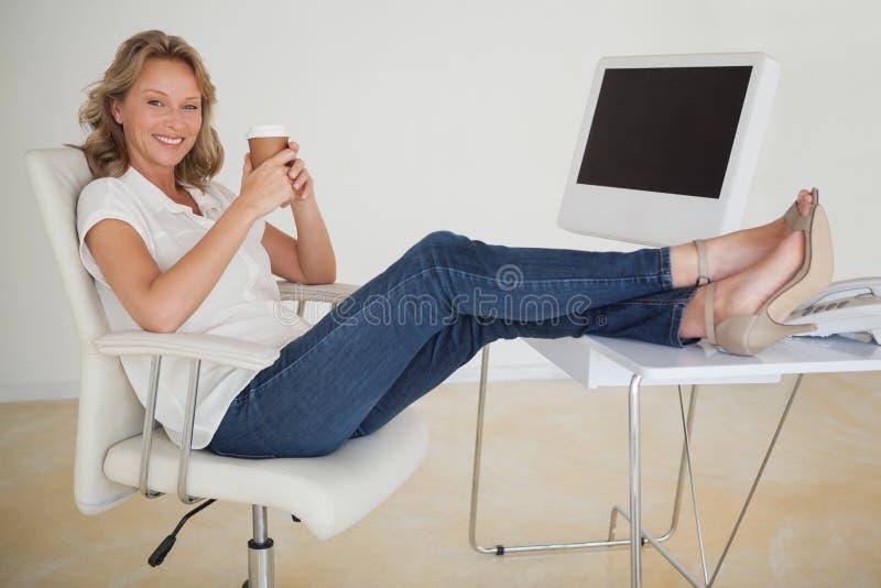 Mulher de negócios ocasional que come um café com seus pés acima na mesa foto de stock