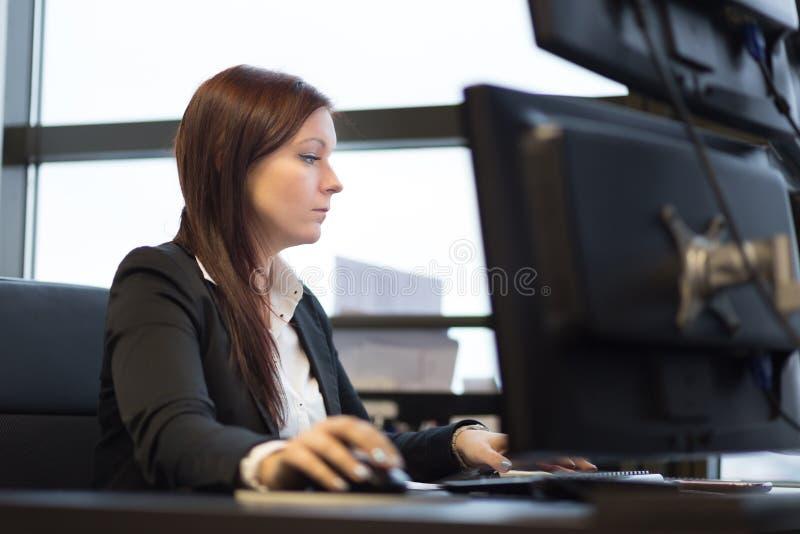 Mulher de negócios ocasional que trabalha no escritório, sentando-se na mesa, datilografando no teclado, olhando o tela de comput imagem de stock