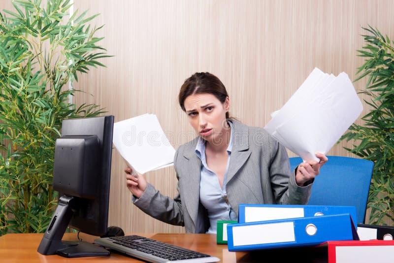 A mulher de negócios ocupada no escritório sob o esforço fotografia de stock