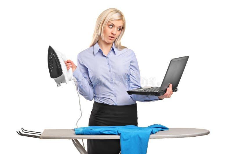 Mulher de negócios ocupada que passa e que trabalha em um portátil foto de stock royalty free
