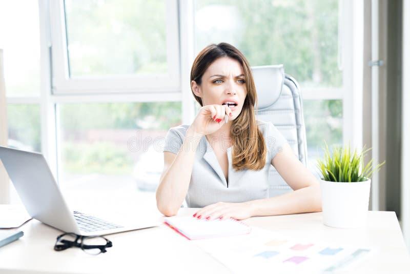 Mulher de negócios olhando de sobrancelhas franzidas no escritório imagem de stock royalty free