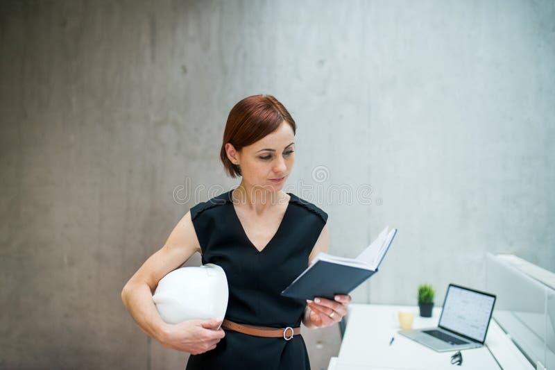 Mulher de negócios ou arquiteto novo com posição do diário e do portátil no escritório fotografia de stock royalty free