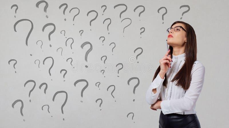 A mulher de negócios pensa em um fundo cinzento foto de stock