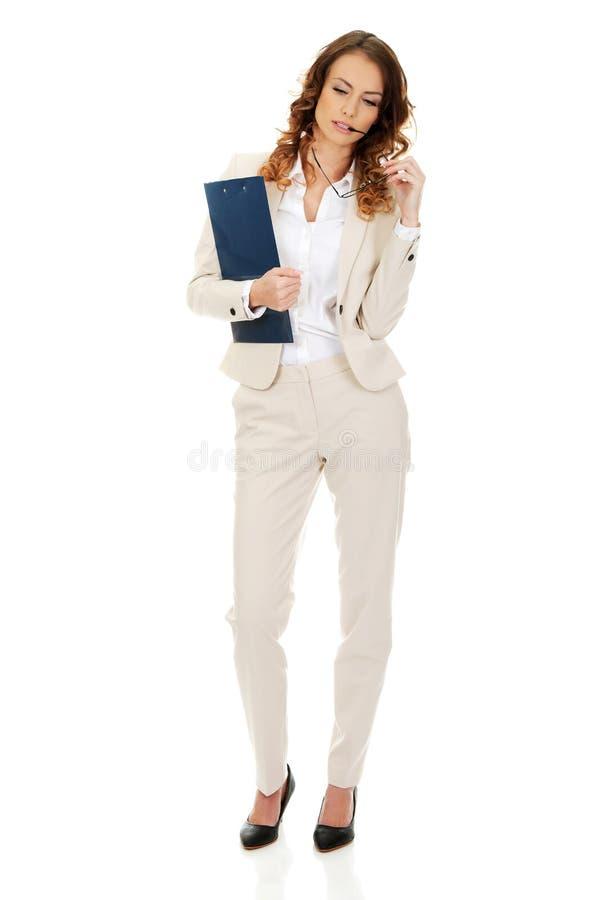 Mulher de negócios pensativa com prancheta imagens de stock royalty free