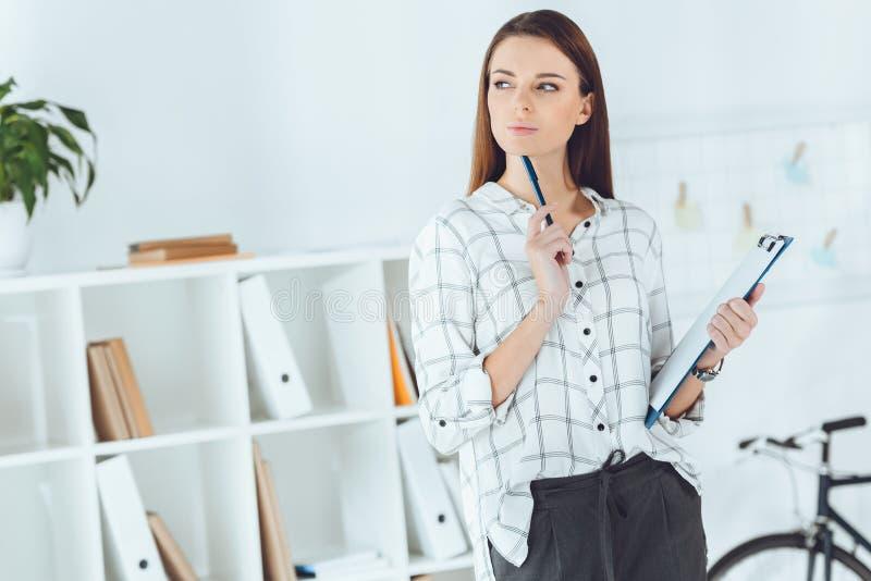 mulher de negócios pensativa com prancheta e lápis fotografia de stock royalty free