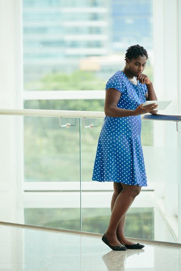 Mulher de negócios pensativa com tabuleta fotografia de stock