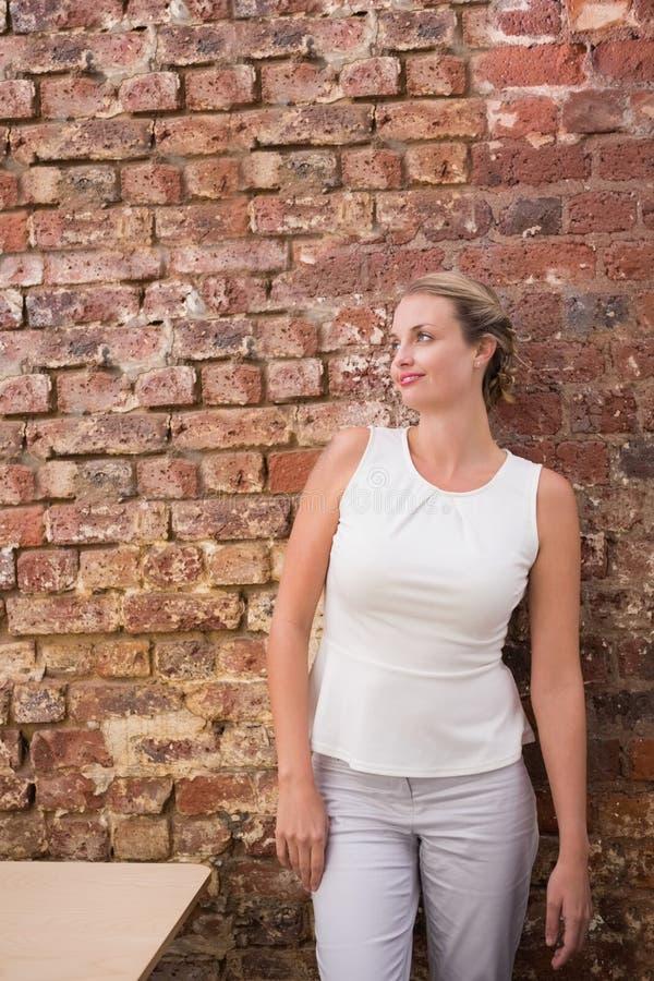 Mulher de negócios pensativa contra a parede de tijolo foto de stock royalty free