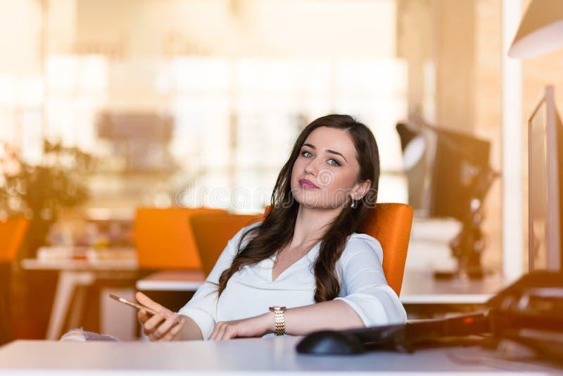 Mulher de negócios pensativa feliz que planeia e que olha lateralmente no escritório imagem de stock royalty free