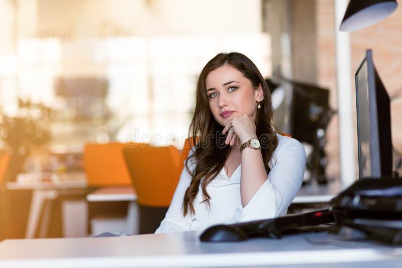 Mulher de negócios pensativa feliz que planeia e que olha lateralmente no escritório fotografia de stock