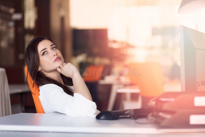 Mulher de negócios pensativa feliz que planeia e que olha lateralmente no escritório imagem de stock
