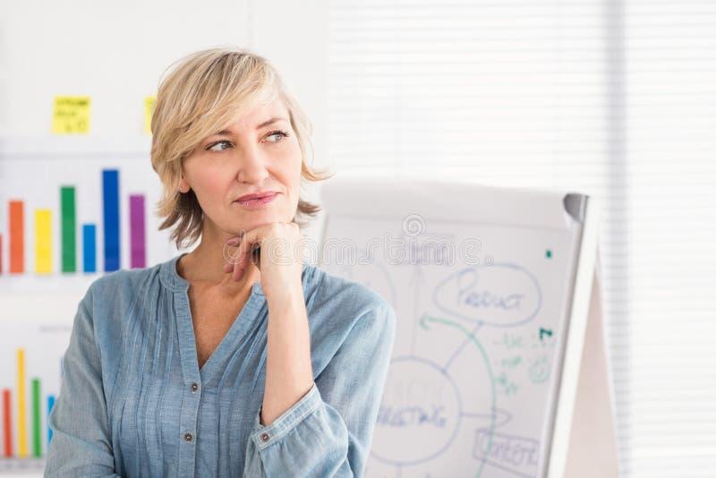 Mulher de negócios pensativa na frente de uma placa branca imagens de stock royalty free