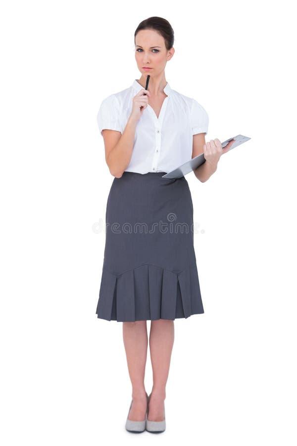 Mulher de negócios pensativa que guardara a prancheta imagem de stock