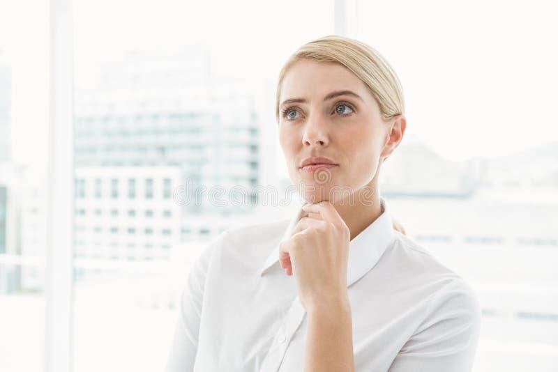 Mulher de negócios pensativa que olha afastado no escritório fotos de stock royalty free