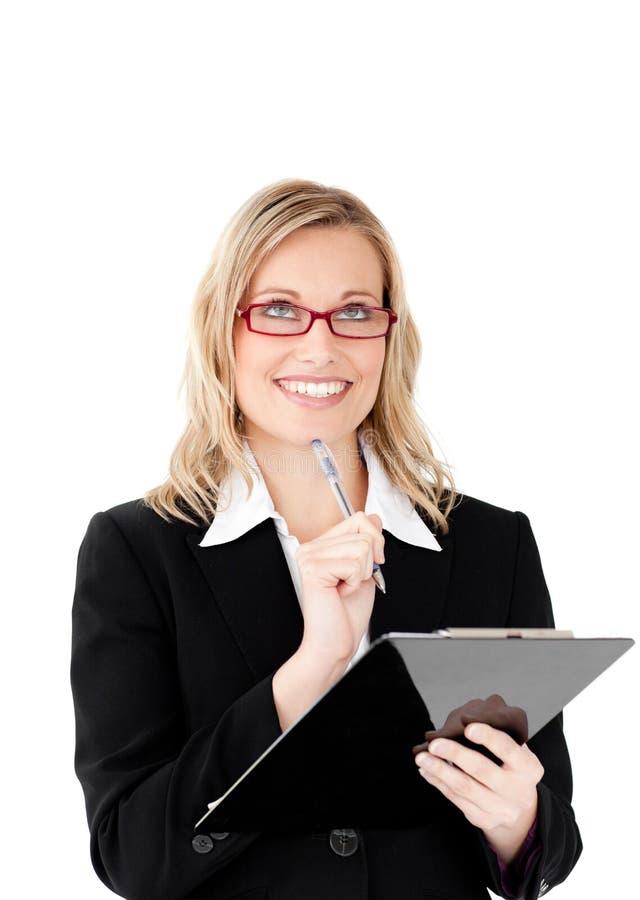 Mulher de negócios pensativa que prende uma prancheta fotos de stock