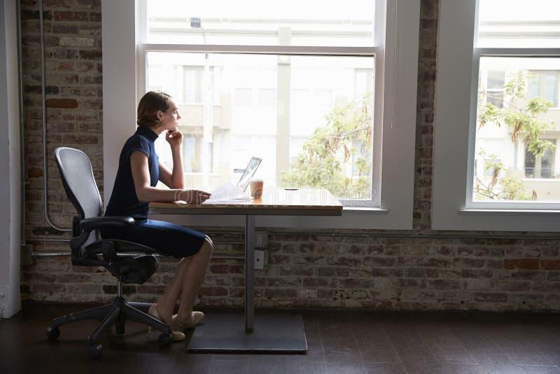 Mulher de negócios pensativa Working On Laptop pela janela fotos de stock royalty free