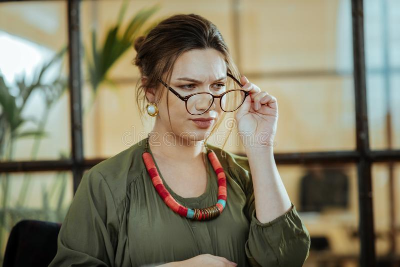 Mulher de negócios próspera nova que põe seus vidros sobre foto de stock royalty free