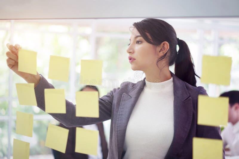 A mulher de negócios prepara a conferência do clique com nota de papel no fundo do escritório da sala de reunião, negócio bem suc fotos de stock