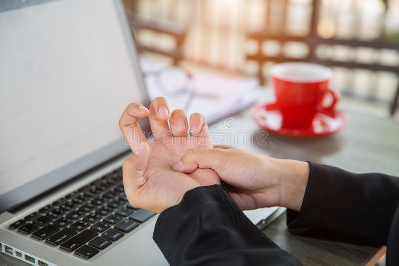 Mulher de negócios pressionando o meio da palma com o polegar para aliviar a dor causada por uma tendinite causada por um uso exc fotos de stock royalty free