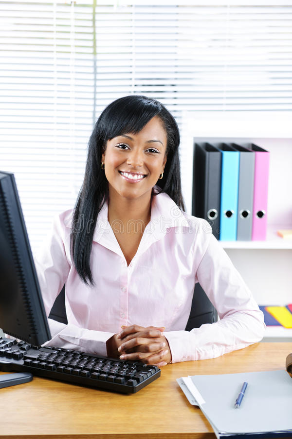 Mulher de negócios preta de sorriso na mesa imagem de stock
