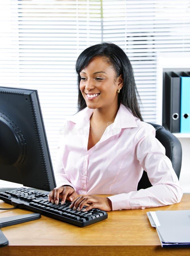 Mulher de negócios preta feliz na mesa imagens de stock royalty free