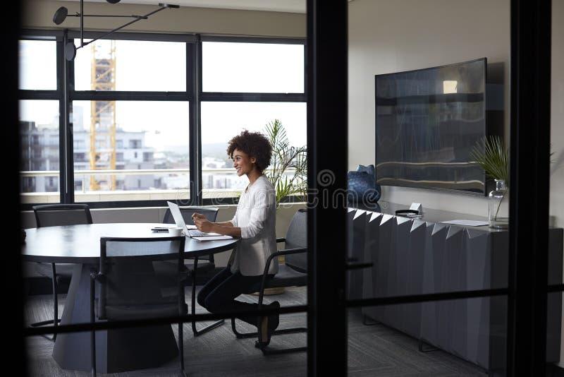 Mulher de negócios preta milenar que trabalha apenas em uma sala de reunião do escritório, parede de vidro completamente vista fotografia de stock royalty free