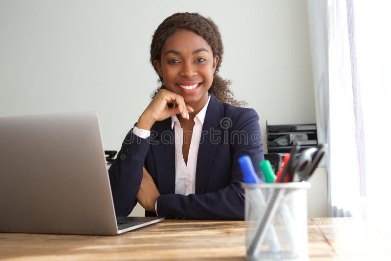 Mulher de negócios preta nova que senta-se na mesa de escritório fotografia de stock