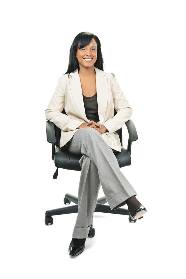 Mulher de negócios preta que senta-se na cadeira do escritório imagem de stock royalty free