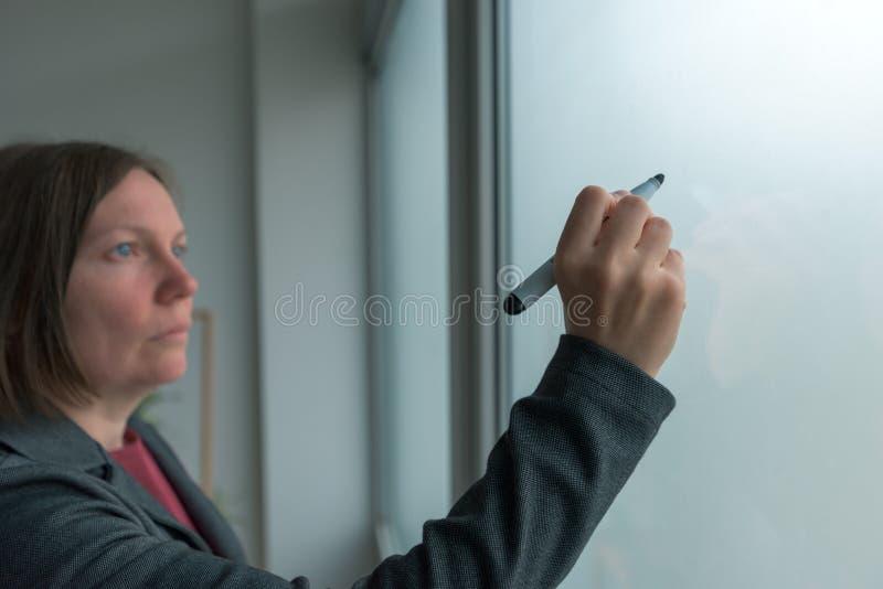 Mulher de negócios pronta para escrever no whiteboard do escritório imagens de stock royalty free