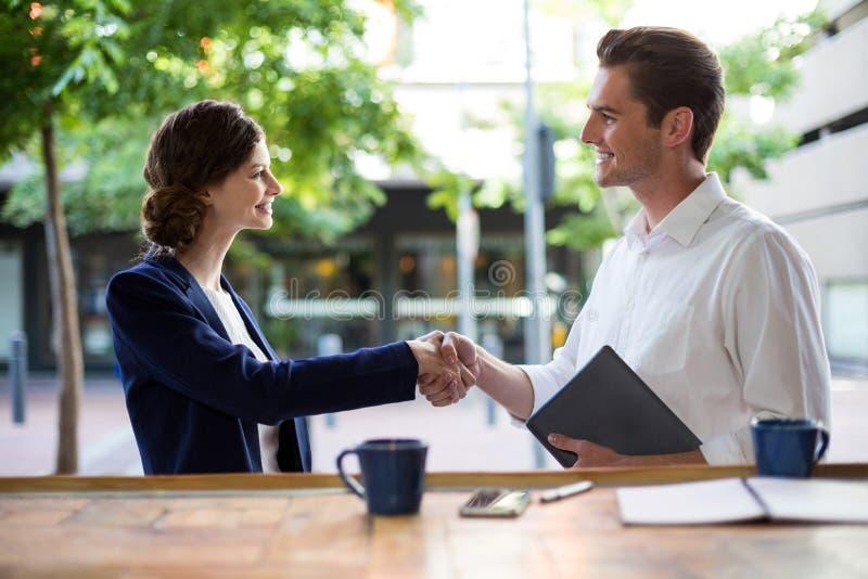 Mulher de negócios que agita as mãos com o homem de negócios no contador fotografia de stock royalty free