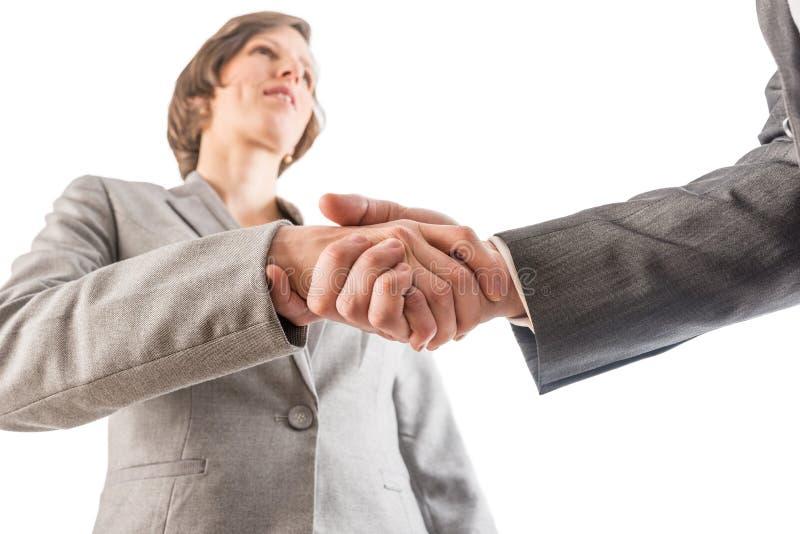 Mulher de negócios que agita as mãos com um homem de negócios como selam um de fotografia de stock