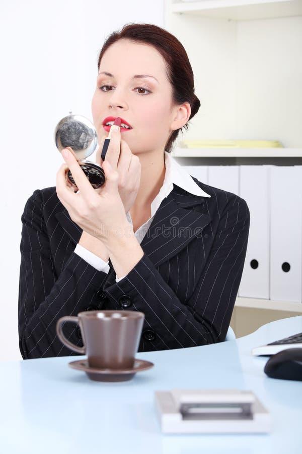 Mulher de negócios que aplica o batom fotografia de stock