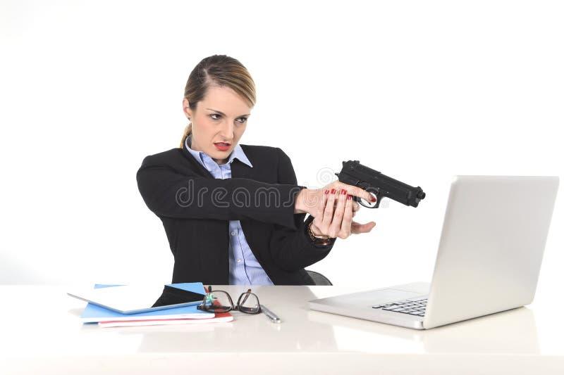 Mulher de negócios que aponta a arma ao portátil do computador que senta-se na mesa de escritório desesperada e forçada fotografia de stock