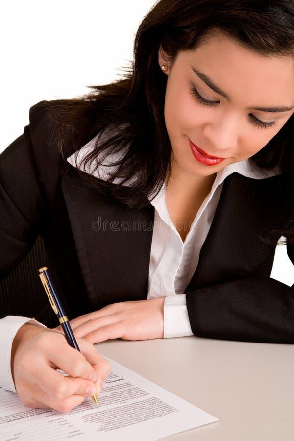 Mulher de negócios que assina um papel foto de stock