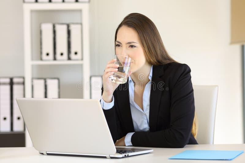 Mulher de negócios que bebe a água fresca em um escritório imagens de stock royalty free