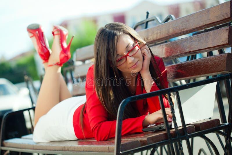 Mulher de negócios que coloca no banco com portátil fotos de stock