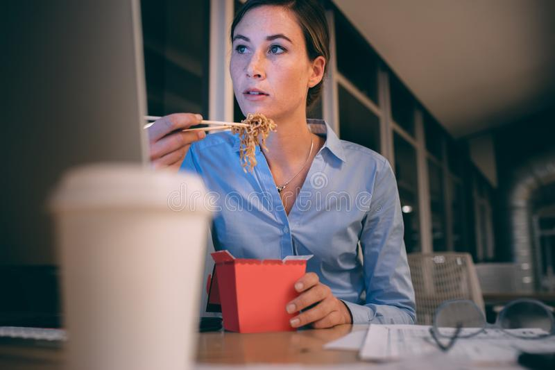 Mulher de negócios que come o alimento ao trabalhar tarde no escritório imagem de stock